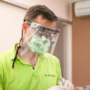 Ein Mediziner trägt ein Faceshield Gesichtsvisier. Darunter trägt er einen Mund-Nasenschutz und eine Brille mit Fokus Linsen