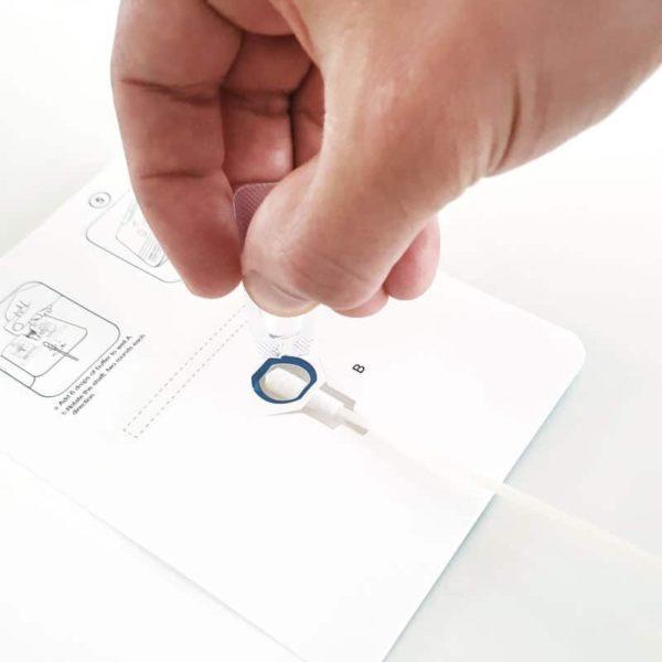 Eine Hand tröpfelt das Probenextrakt auf die Testkassette